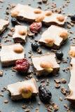 Μαύρη σοκολάτα με τα καρύδια και τους ξηρούς καρπούς σε ένα υπόβαθρο cru στοκ εικόνες με δικαίωμα ελεύθερης χρήσης