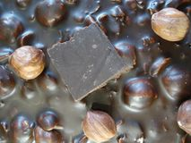Μαύρη σοκολάτα με τα φουντούκια Ένα κομμάτι της σοκολάτας σε έναν φραγμό σοκολάτας επάνω από την όψη Στοκ Εικόνες