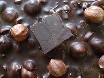 Μαύρη σοκολάτα με τα φουντούκια Ένα κομμάτι της σοκολάτας σε έναν φραγμό σοκολάτας Στοκ Εικόνα