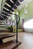 Μαύρη, σφυρηλατημένη σκάλα σε ένα υψηλό, πράσινο εσωτερικό στοκ φωτογραφία