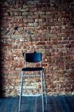 Μαύρη σύγχρονη καρέκλα στο υπόβαθρο τουβλότοιχος Στοκ εικόνα με δικαίωμα ελεύθερης χρήσης