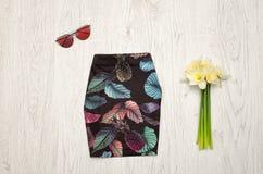 Μαύρη φούστα με τους ανανάδες, τα γυαλιά και μια ανθοδέσμη των daffodils μοντέρνη έννοια Ξύλινη ανασκόπηση στοκ εικόνες