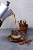Μαύρη arabica έκχυση καφέ από τον κατασκευαστή καφέ στο φλυτζάνι και ομο Στοκ Φωτογραφία