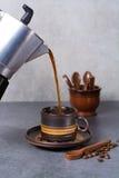 Μαύρη arabica έκχυση καφέ από τον κατασκευαστή καφέ στο φλυτζάνι και ομο Στοκ Φωτογραφίες