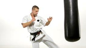 Μαύρη karate ζωνών άσκηση ατόμων sandbag επάνω φιλμ μικρού μήκους