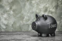 Μαύρη piggy τράπεζα με τους ΦΟΡΟΥΣ λέξης στοκ φωτογραφίες με δικαίωμα ελεύθερης χρήσης