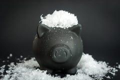 Μαύρη piggy τράπεζα στο χιονισμένο πίνακα Στοκ φωτογραφία με δικαίωμα ελεύθερης χρήσης