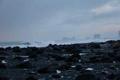 Μαύροι βράχοι με τη συντριβή των κυμάτων στο υπόβαθρο στην παραλία Reynisfjara στην Ισλανδία στοκ εικόνες