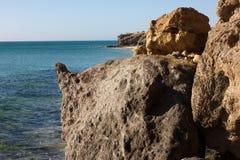 Μαύροι βράχοι της παραλίας Calma πλευρών μπλε ακτή Playa Barca, Fuerteventura, Κανάρια νησιά, Ισπανία Λα Istmo de που καθαρίζεται Στοκ Φωτογραφία