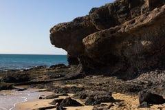 Μαύροι βράχοι της παραλίας Calma πλευρών μπλε ακτή Playa Barca, Fuerteventura, Κανάρια νησιά, Ισπανία Λα Istmo de που καθαρίζεται Στοκ Φωτογραφίες