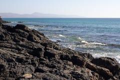 Μαύροι βράχοι της παραλίας Calma πλευρών μπλε ακτή Playa Barca, Fuerteventura, Κανάρια νησιά, Ισπανία Λα Istmo de που καθαρίζεται Στοκ φωτογραφία με δικαίωμα ελεύθερης χρήσης