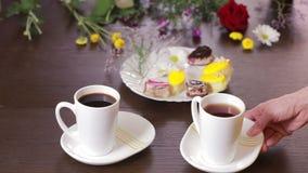 Μαύροι τσάι και καφές στις κούπες πίνακας με ένα ποτό και ένα επιδόρπιο επάνω από την όψη φιλμ μικρού μήκους