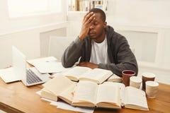 Μαύρος άνδρας σπουδαστής που μελετά στο επιτραπέζιο σύνολο των βιβλίων Στοκ φωτογραφίες με δικαίωμα ελεύθερης χρήσης