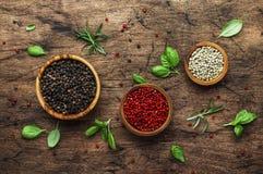 Μαύρος, άσπρος και ρόδινος αυξήθηκε πιπέρια στα κύπελλα, ανάμεικτα καρυκεύματα και τα πικάντικα χορτάρια στον ξύλινο αγροτικό πίν στοκ φωτογραφία με δικαίωμα ελεύθερης χρήσης