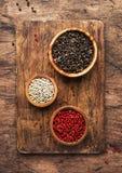 Μαύρος, άσπρος και ρόδινος αυξήθηκε πιπέρια στα κύπελλα, ανάμεικτα καρυκεύματα και τα πικάντικα χορτάρια στον ξύλινο αγροτικό πίν στοκ φωτογραφίες