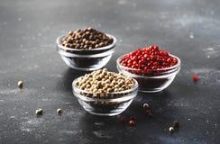 Μαύρος, άσπρος και ρόδινος αυξήθηκε πιπέρια στα κύπελλα, ανάμεικτα καρυκεύματα στον γκρίζο πίνακα κουζινών, εκλεκτική εστίαση στοκ εικόνα