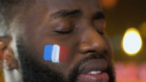 Μαύρος αρσενικός ανεμιστήρας με τη γαλλική σημαία στο μάγουλο που ανατρέπεται για την απώλεια εθνικών ομάδων, αθλητισμός απόθεμα βίντεο