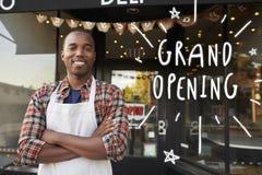 Μαύρος αρσενικός ιδιοκτήτης επιχείρησης έξω από το μεγάλο άνοιγμα καφετεριών στοκ εικόνα