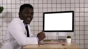 Μαύρος γιατρός που μιλά στη συνεδρίαση καμερών δίπλα στη οθόνη υπολογιστή Άσπρη παρουσίαση απόθεμα βίντεο