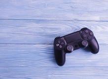 Μαύρος ελεγκτής παιχνιδιών στα ξύλινα πολυμέσα υποβάθρου στοκ φωτογραφία με δικαίωμα ελεύθερης χρήσης