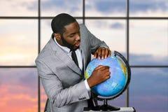 Μαύρος επιχειρηματίας που δείχνει στη σφαίρα Στοκ Φωτογραφίες