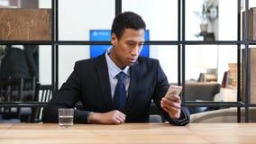 Μαύρος επιχειρηματίας που κοιτάζει βιαστικά σε Smartphone Στοκ εικόνες με δικαίωμα ελεύθερης χρήσης
