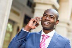 Μαύρος επιχειρηματίας που μιλά με το έξυπνο τηλέφωνό του στο αστικό backgrou Στοκ φωτογραφία με δικαίωμα ελεύθερης χρήσης