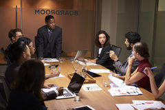 Μαύρος επιχειρηματίας που στέκεται να απευθυνθεί στους συναδέλφους στη συνεδρίαση Στοκ Εικόνες