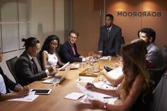 Μαύρος επιχειρηματίας που στέκεται να απευθυνθεί στους συναδέλφους στη συνεδρίαση Στοκ Φωτογραφία