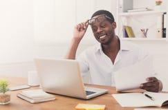 Μαύρος επιχειρηματίας στην αρχή, εργασία με το lap-top και έγγραφα Στοκ Εικόνα