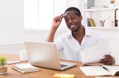 Μαύρος επιχειρηματίας στην αρχή, εργασία με το lap-top και έγγραφα Στοκ φωτογραφίες με δικαίωμα ελεύθερης χρήσης