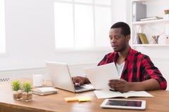 Μαύρος επιχειρηματίας στο περιστασιακό γραφείο, εργασία με το lap-top και έγγραφα Στοκ φωτογραφία με δικαίωμα ελεύθερης χρήσης