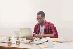 Μαύρος επιχειρηματίας στο περιστασιακό γραφείο, εργασία με το lap-top Στοκ εικόνα με δικαίωμα ελεύθερης χρήσης
