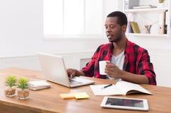 Μαύρος επιχειρηματίας στο περιστασιακό γραφείο, εργασία με το lap-top Στοκ Εικόνες