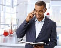 Μαύρος επιχειρηματίας στο τηλέφωνο στο λόμπι γραφείων Στοκ Εικόνες