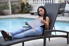 Μαύρος θηλυκός τουρίστας που διαβάζει ένα φυλλάδιο ξενοδοχείων Στοκ φωτογραφία με δικαίωμα ελεύθερης χρήσης