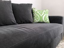 Μαύρος καναπές με το πράσινο μαξιλάρι Στοκ Εικόνες