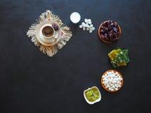 Μαύρος καφές, γάλα, ημερομηνίες και τουρκικά γλυκά σε ένα μαύρο υπόβαθρο Γλυκά τρόφιμα για ramadan Στοκ φωτογραφία με δικαίωμα ελεύθερης χρήσης