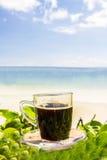 Μαύρος καφές με την άποψη σχετικά με την παραλία και το μπλε ουρανό Στοκ εικόνες με δικαίωμα ελεύθερης χρήσης