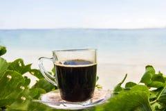 Μαύρος καφές με την άποψη σχετικά με την παραλία και το μπλε ουρανό Στοκ φωτογραφία με δικαίωμα ελεύθερης χρήσης