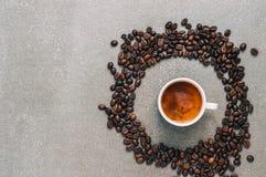 Μαύρος καφές με την κρέμα σε ένα γκρίζο υπόβαθρο που περιβάλλεται από τα φασόλια καφέ, τοπ άποψη στοκ εικόνα με δικαίωμα ελεύθερης χρήσης