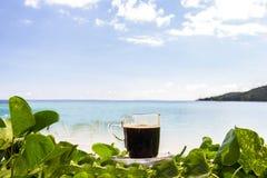 Μαύρος καφές με τις απόψεις σχετικά με την παραλία και το μπλε ουρανό Στοκ Εικόνες