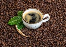 Μαύρος καφές με το πράσινο υπόβαθρο φασολιών caffee φύλλων Στοκ Εικόνες