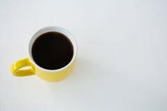 Μαύρος καφές που εξυπηρετείται στο κίτρινο φλυτζάνι Στοκ Εικόνα