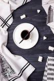 Μαύρος καφές σε ένα άσπρες φλυτζάνι, ένα φασόλι βανίλιας, marshmallow και μια πετσέτα κουζινών μαύρος-λευκού σε ένα σκοτεινό υπόβ Στοκ Εικόνες