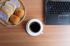 Μαύρος καφές σε ένα άσπρους φλυτζάνι, ένα ψωμί, και έναν φορητό προσωπικό υπολογιστή στοκ φωτογραφίες με δικαίωμα ελεύθερης χρήσης