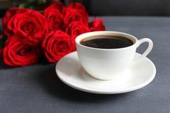 Μαύρος καφές σε ένα άσπρο φλυτζάνι με ένα πιατάκι στον πίνακα, μια ανθοδέσμη των κόκκινων τριαντάφυλλων στοκ εικόνες