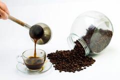 Μαύρος καφές σε ένα φλυτζάνι γυαλιού και τα σιτάρια του καφέ σε ένα άσπρο υπόβαθρο Στοκ φωτογραφία με δικαίωμα ελεύθερης χρήσης