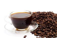 Μαύρος καφές σε ένα φλυτζάνι γυαλιού και τα σιτάρια του καφέ σε ένα άσπρο υπόβαθρο Στοκ φωτογραφίες με δικαίωμα ελεύθερης χρήσης