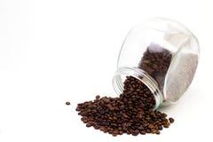 Μαύρος καφές σε ένα φλυτζάνι γυαλιού και τα σιτάρια του καφέ σε ένα άσπρο υπόβαθρο Στοκ Φωτογραφία